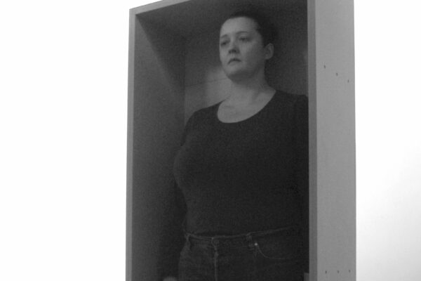 A photograph of a woman standing in a human-sized box