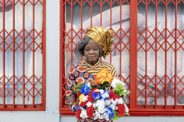 A woman stands on the street, holding a bunch of plastic flowers, and stands against a white wall with red window shutters
